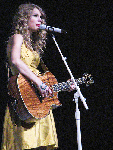 Taylor Swift perfomance onstage in a yellow dress