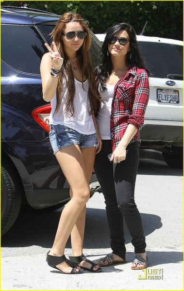 Miley Cyrus with her friend smile for the cameras