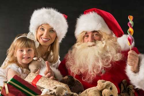 Santa Claus sitting at home with family - little girl and her mother and giving gifts